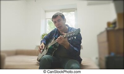 Man playing an acoustic guitar. Man Playing Acoustic Guitar lifestyle Close Up slow motion video. in the room sits on the couch. man and guitar concept