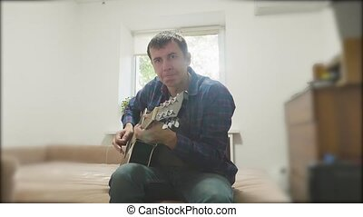 Man playing an acoustic guitar. Man Playing Acoustic lifestyle Guitar Close Up slow motion video. in the room sits on the couch. man and guitar concept