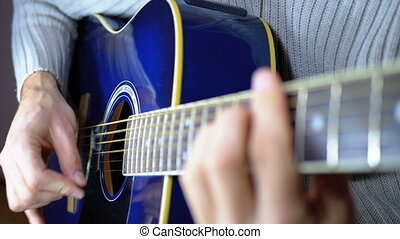 Man Playing an Acoustic Guitar. Slow movement of the...