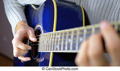 Man Playing an Acoustic Guitar. Slow movement of the vibrating string. Slow motion