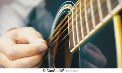 Man Playing an Acoustic Guitar with a Mediator