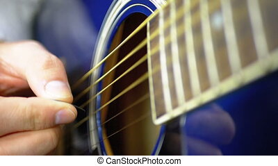 Man Playing an Acoustic Guitar with a Mediator. Slow motion...