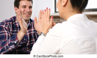 Man playing and clapping with a woman