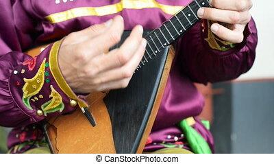Man playing balalaika. - Man playing balalaika on the...