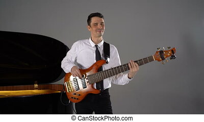 Male musician plays bass guitar on grey background next to piano