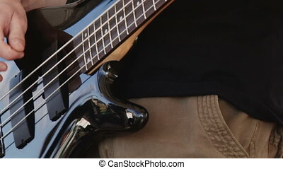 Man playing black bass guitar, fast zoom in, details