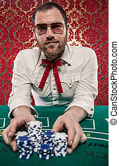 Man Playing Blackjack Bets All - A man wearing glasses, a...