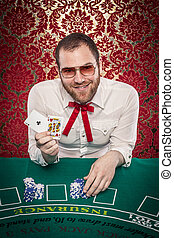 Man Playing Blackjack Winning Hand - A man wearing glasses,...