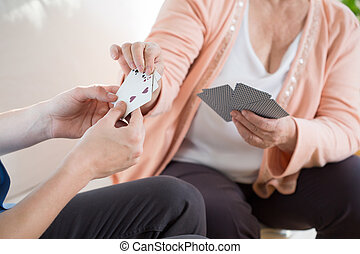 Man playing cards with older woman