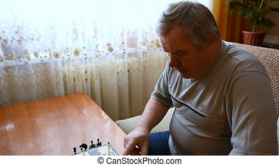 Man playing chess at home