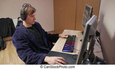 Man playing computer games in headphones at home