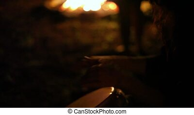 Man playing djembe in front of a fire at night