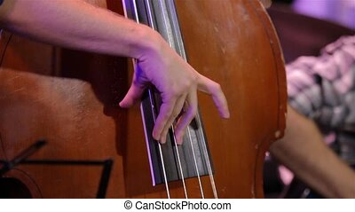Male hands playing old shabby brown double bass