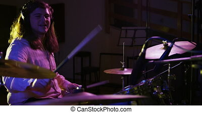 Side view of a Caucasian man with long dark hair wearing headphones and playing a drum kit during a session at a recording studio. Musicians working on producing a song