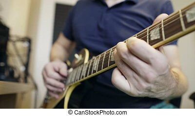 Man playing electric guitar - Closeup cropped video of a man...