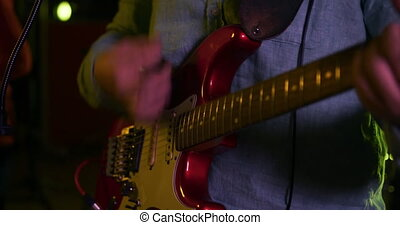 Man playing electric guitar in a music studio