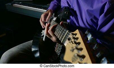 man playing electric guitar recording studio