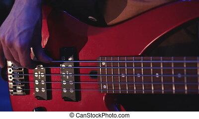 Man playing electrical bass guitar. Bass Guitar closeup.