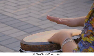 Man playing ethnic drum on street - Unrecognizable man...