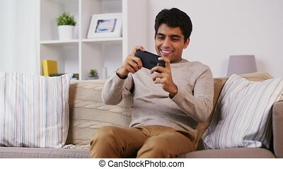 man playing game on smartphone at home - technology, people...