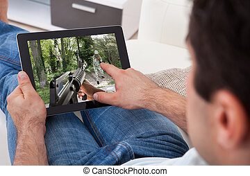 Man Playing Game On Tablet Pc - Close-up Of Young Man...