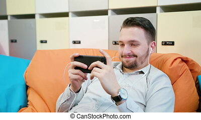 Man Playing Games on the Smartphone Indoors