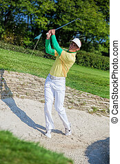 Man playing golf from bunker