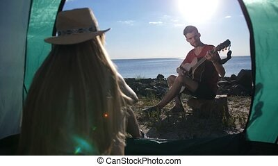 Man playing guitar and singing to girl in tent