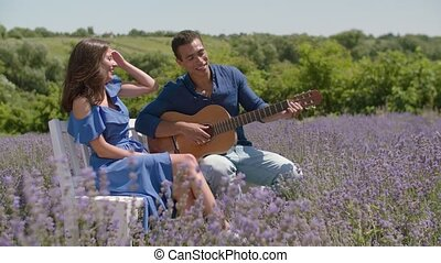 Man playing guitar and singing to woman in nature