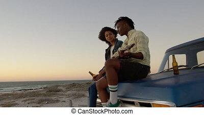 Man playing guitar and woman singing a song on pickup truck bonnet 4k