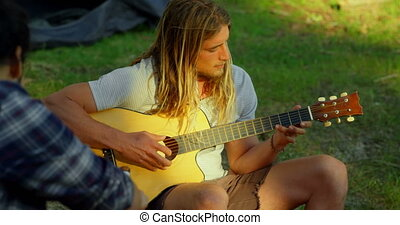Man playing guitar at camp in the forest 4k