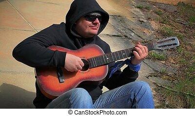 Man playing guitar at outdoors
