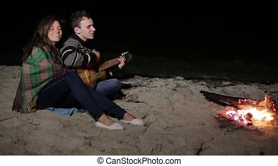 Man playing guitar by the fire and the sea