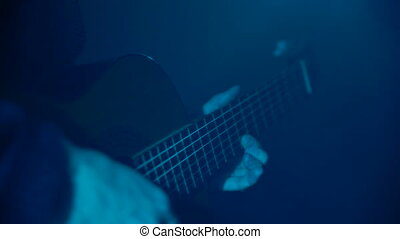 Man playing guitar close-up - A man is playing an acoustic...
