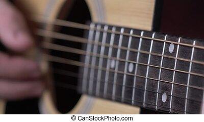 Man playing guitar, dynamic change of focus, close up - Man...