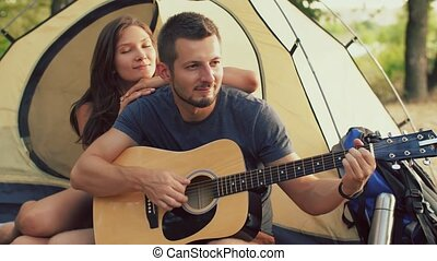 Man playing guitar for his girlfriend sitting at the camping...