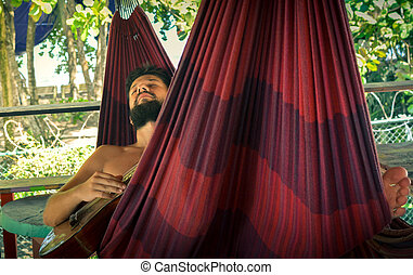 man playing guitar in a hammock