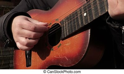 Man playing guitar in autumn day