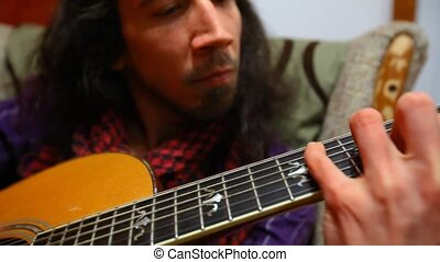 Man playing guitar in living room.