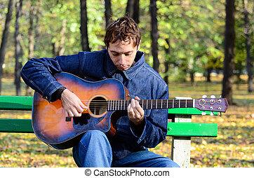 Man playing guitar in park