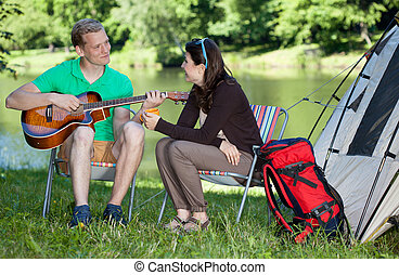 Man playing guitar song for woman