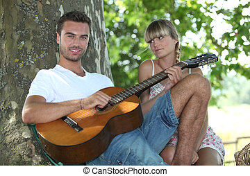Man playing guitar under a tree