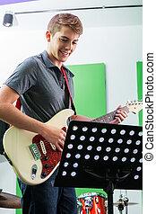 Man Playing Guitar While Looking At Musical Notes