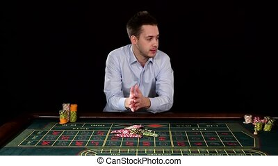 Man playing in the casino and wins. Black
