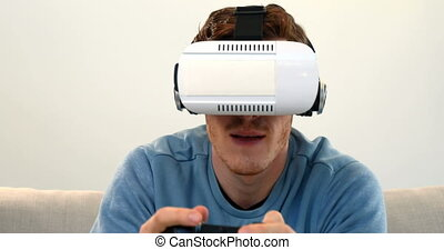 Man playing joystick game with virtual reality headset on...