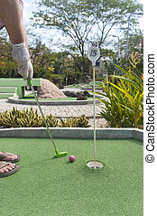 Man Playing Mini Golf with Gloves