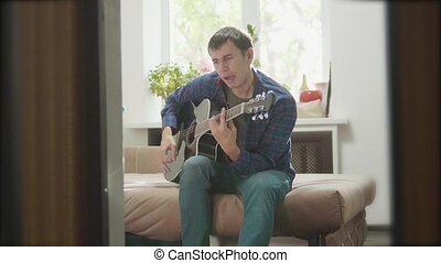 man playing music by wooden acoustic guitar. Man Playing Acoustic Guitar Close Up slow lifestyle motion video. in the room sits on the couch. man and guitar concept