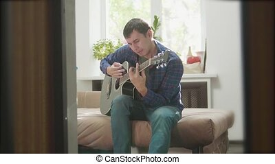 man playing music by wooden acoustic guitar. Man Playing Acoustic Guitar Close Up slow motion lifestyle video. in the room sits on the couch. man and guitar concept