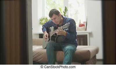 man playing music by wooden acoustic guitar. Man Playing Acoustic Guitar Close Up slow motion video. in the room sits on the couch. man and lifestyle guitar concept