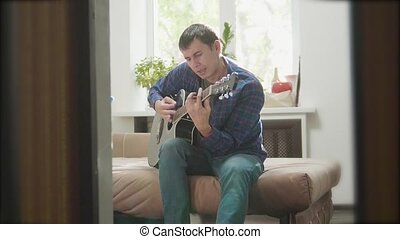 man playing music by wooden acoustic guitar. Man Playing Acoustic Guitar Close Up slow motion video lifestyle. in the room sits on the couch. man and guitar concept